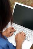 Escritura china joven de la mujer en una computadora portátil al aire libre fotografía de archivo