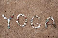 Escritura con yoga del texto de las cáscaras en la playa Imagenes de archivo