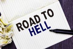 Escritura conceptual de la mano que muestra el camino al infierno Marcador inseguro aventurado oscuro o del viaje del callejón ex foto de archivo libre de regalías