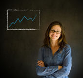 Escritura confiada de la mujer en fondo de la pizarra con el gráfico Fotos de archivo