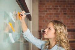 Escritura creativa de la empresaria en notas pegajosas en oficina Fotos de archivo
