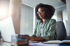 Escritura creativa de la empresaria usando el ordenador portátil en el escritorio de oficina imagenes de archivo