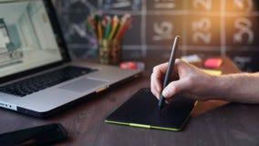 Escritura creativa del hombre de negocios en la tableta gráfica mientras que usa el ordenador portátil en oficina metrajes