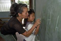 Escritura de ayuda del alumno del profesor en la pizarra Fotos de archivo libres de regalías