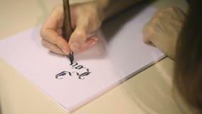 Escritura de caligrafía gótica la mano femenina escribe con la pluma de la tinta almacen de video