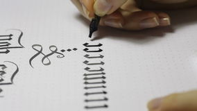 Escritura de caligrafía gótica la mano femenina escribe con la pluma de la tinta metrajes