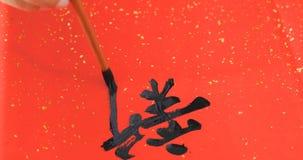 Escritura de la caligrafía china por Año Nuevo lunar, el significar de las palabras de Imagen de archivo libre de regalías