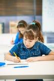 Escritura de la chica joven en la escuela Fotografía de archivo libre de regalías