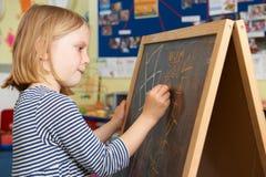 Escritura de la chica joven en la pizarra en sala de clase de la escuela Foto de archivo libre de regalías