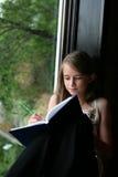 Escritura de la chica joven en su diario Fotos de archivo libres de regalías