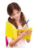 Escritura de la colegiala en cuaderno Fotografía de archivo libre de regalías