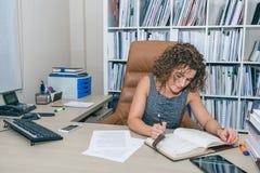 Escritura de la empresaria en el cuaderno que se sienta en la oficina Fotos de archivo