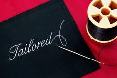 Escritura de la etiqueta adaptada en la guarnición de seda roja Imágenes de archivo libres de regalías