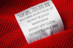 Escritura de la etiqueta de cuidado del lavadero en el fondo blanco Foto de archivo libre de regalías