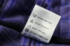 Escritura de la etiqueta de cuidado del lavadero en fondo escocés de la materia textil Foto de archivo libre de regalías