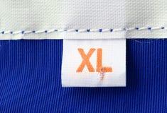Escritura de la etiqueta de la ropa de la talla del XL Imagen de archivo libre de regalías