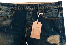 Escritura de la etiqueta de los pantalones vaqueros del papel de la etiqueta del espacio en blanco del detalle de los tejanos Fotos de archivo libres de regalías