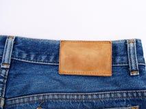 Escritura de la etiqueta en blanco del cuero de los pantalones vaqueros en tela de la mezclilla Fotografía de archivo libre de regalías