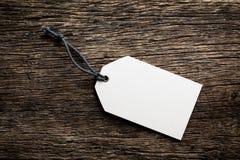 Escritura de la etiqueta en blanco del precio en fondo de madera Imagen de archivo