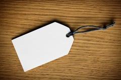 Escritura de la etiqueta en blanco del precio en fondo de madera Fotos de archivo libres de regalías
