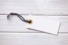 Escritura de la etiqueta en blanco del precio en fondo de madera Foto de archivo libre de regalías