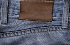 Escritura de la etiqueta en los pantalones vaqueros Imagen de archivo libre de regalías