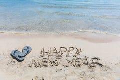 Escritura de la Feliz Año Nuevo en la arena Foto de archivo