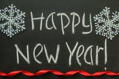 Escritura de la Feliz Año Nuevo en una pizarra Imagenes de archivo