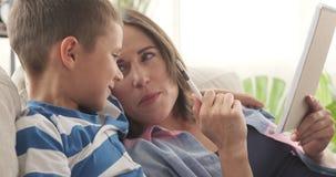 Escritura de la madre y del hijo para hacer la lista en libreta almacen de metraje de vídeo
