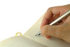 Escritura de la mano con una pluma Fotografía de archivo libre de regalías