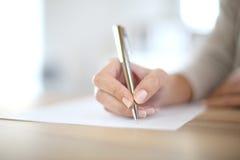 Escritura de la mano de la mujer con la pluma Foto de archivo libre de regalías
