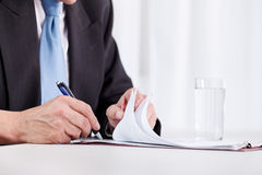 Escritura de la mano del hombre de negocios en el papel Imagen de archivo libre de regalías