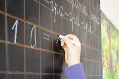 Escritura de la mano del niño en la pizarra Foto de archivo