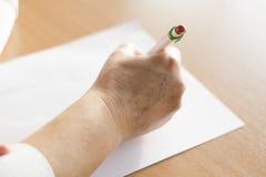 Escritura de la mano del ` s de la mujer del primer en el papel Fotografía de archivo