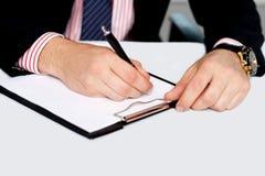 Escritura de la mano del varón en la libreta en blanco Imagen de archivo libre de regalías
