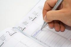 Escritura de la mano en agenda Fotografía de archivo libre de regalías