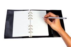 Escritura de la mano en cuaderno Foto de archivo libre de regalías