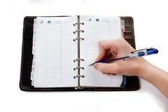 Escritura de la mano en cuaderno abierto Foto de archivo libre de regalías