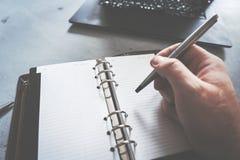 Escritura de la mano en cuaderno con el ordenador portátil como fondo fotos de archivo