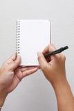 Escritura de la mano en el cuaderno Fotos de archivo libres de regalías