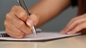Escritura de la mano en el papel almacen de metraje de vídeo