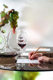 Escritura de la mano en el papel en la degustación de vinos Imagenes de archivo