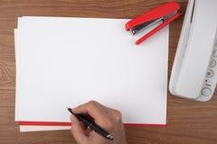 Escritura de la mano en las hojas de papel que simbolizan la firma del documento Fotografía de archivo