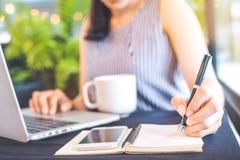 Escritura de la mano de la mujer en la libreta con una pluma y trabajos en un ordenador portátil c Fotografía de archivo libre de regalías
