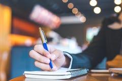 escritura de la mano de la mujer de negocios en la libreta con una pluma Fotos de archivo libres de regalías