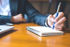 escritura de la mano de la mujer de negocios en la libreta con una pluma Imagenes de archivo