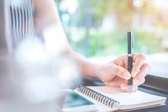 Escritura de la mano de la mujer de negocios en la libreta con una pluma en la oficina Imagen de archivo