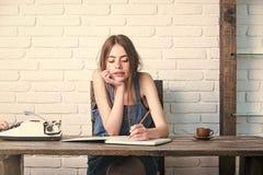 Escritura de la muchacha con el lápiz en cuaderno Fotografía de archivo libre de regalías