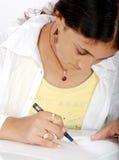 Escritura de la muchacha con la pluma Imagen de archivo libre de regalías