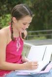 Escritura de la muchacha de la escuela en cuaderno al aire libre Imágenes de archivo libres de regalías